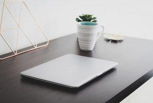 Zaklopljen laptop na stolu pored koga je šolja za kafu